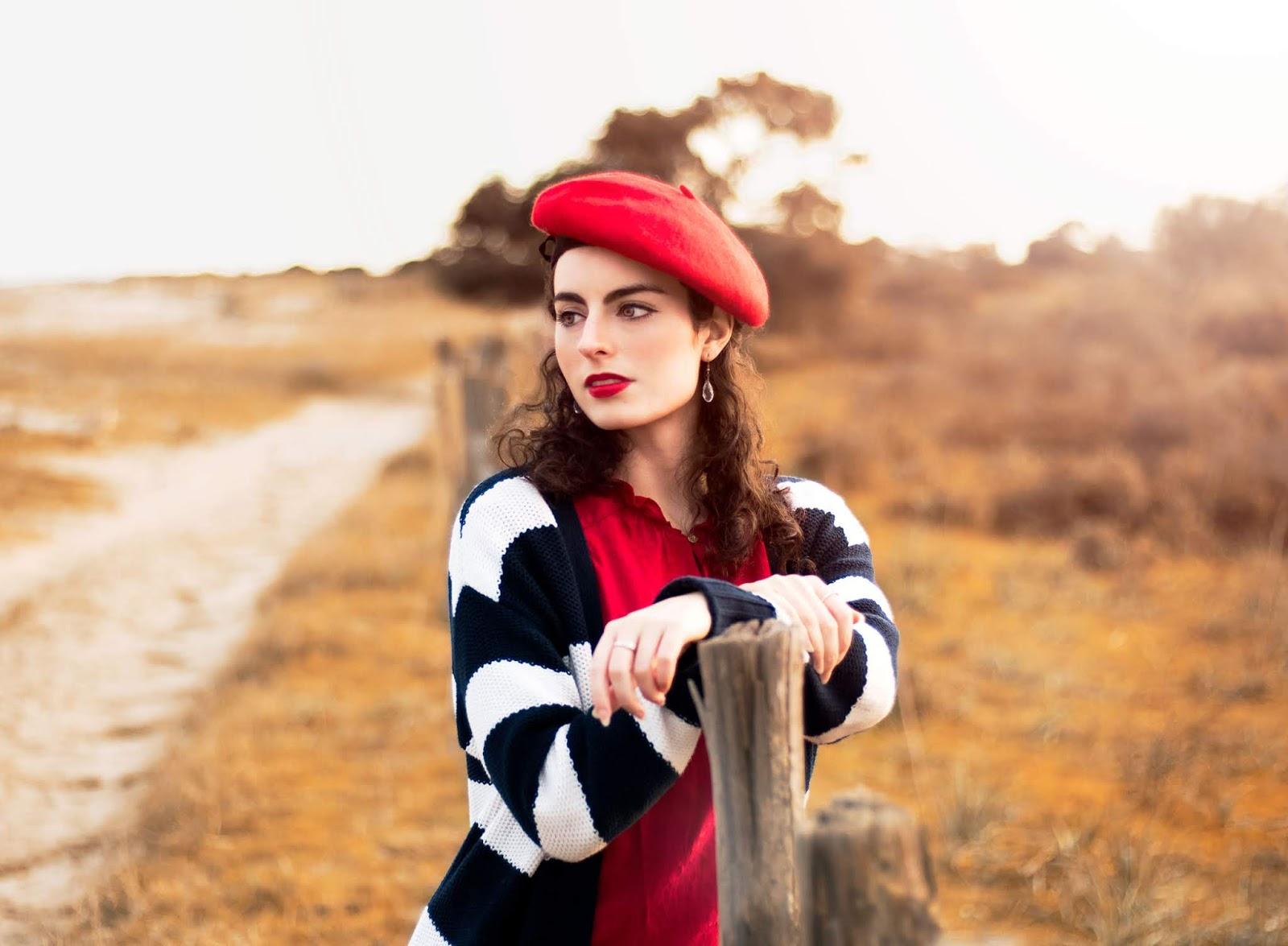 Béret rouge, gilet long rayé marin, blouse rouge, jeans et bottines marrons.