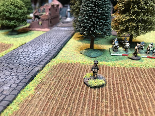 The British platoon commander moves in behind the riflemen and bombers