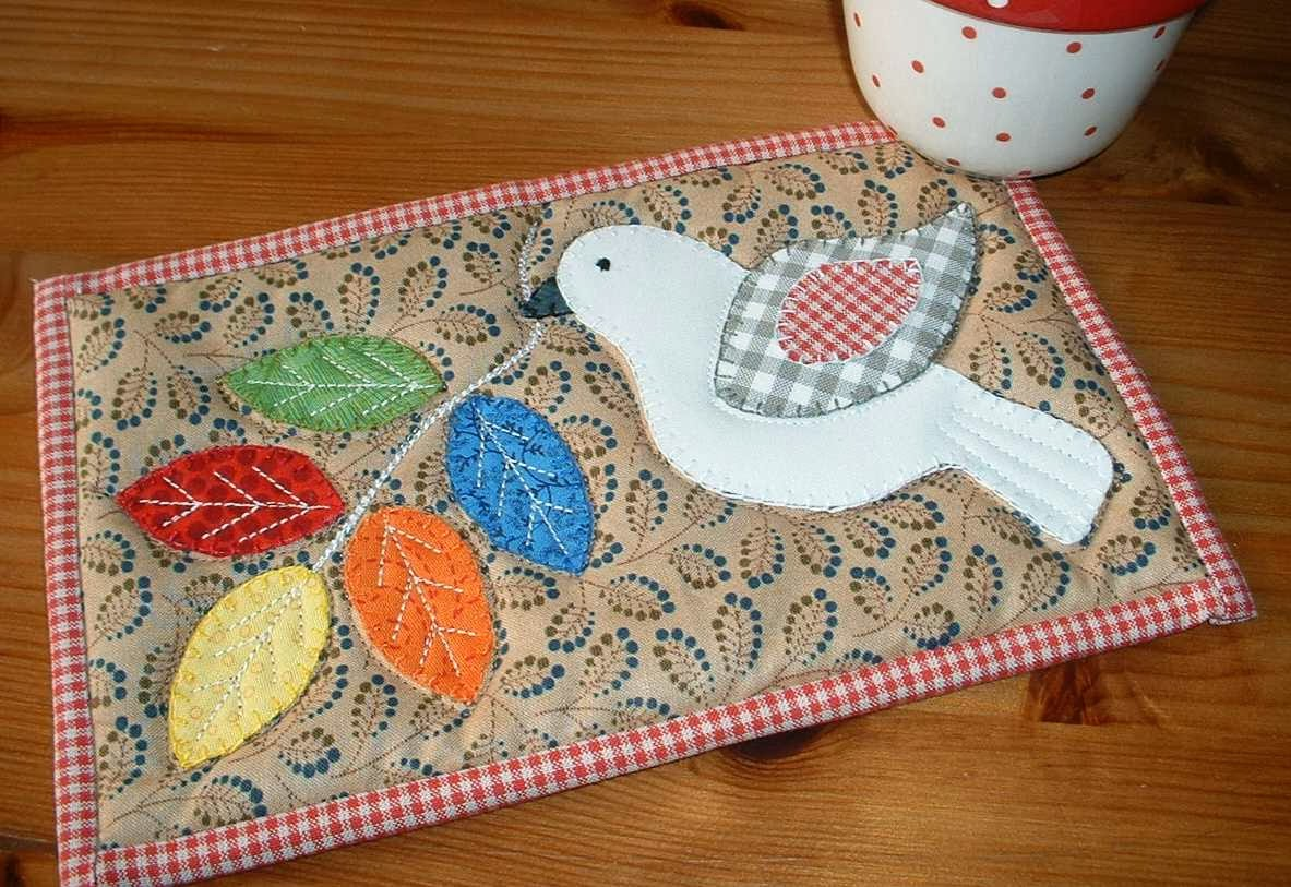 http://www.craftsy.com/pattern/quilting/home-decor/winter-dove-mug-rug/83431