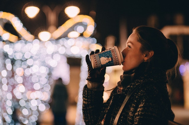 Mujer bebiendo sobre fondo de arbor de Navidad iluminado en una ciudad