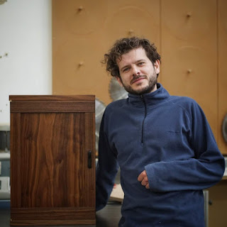 Man standing beside a small walnut drinks cabinet