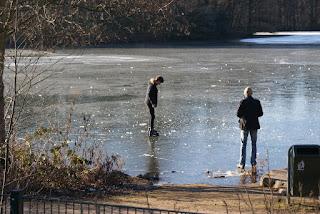Ein Junge steht mit Schlittschuhen auf der Eisfläche eines Sees.