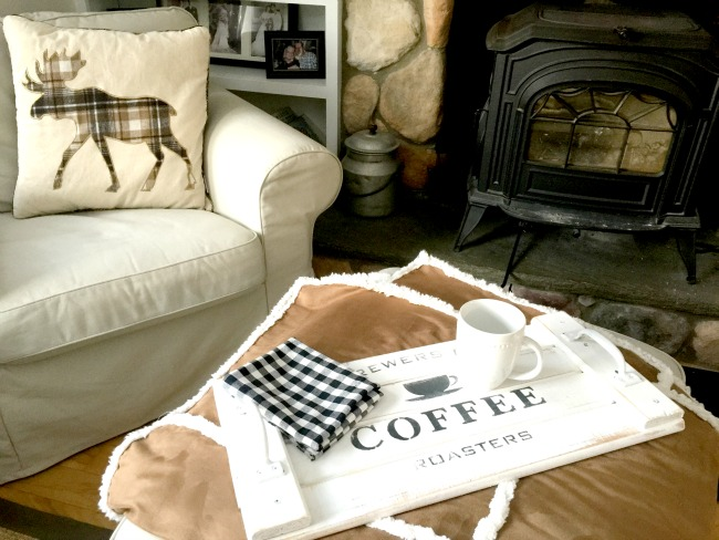 White coffee tray in front of chair and wood burning stove