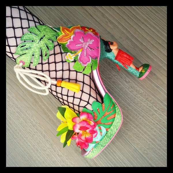 close up of floral and fruity shoe with grass skirt hula girl heels on one foot wearing fishnet tights