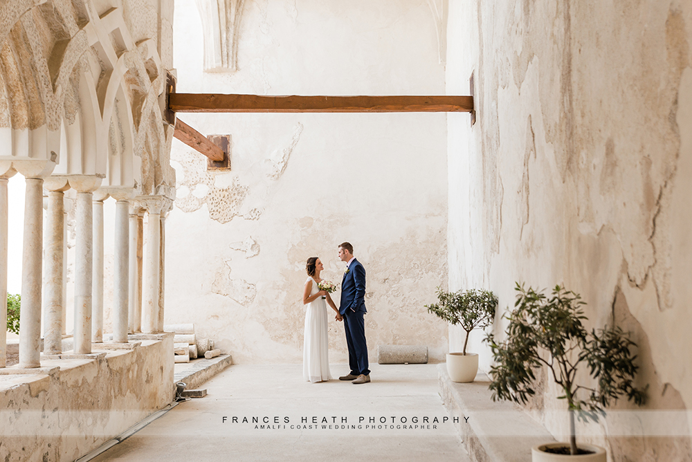 Wedding portrait of bride and groom in cloisters