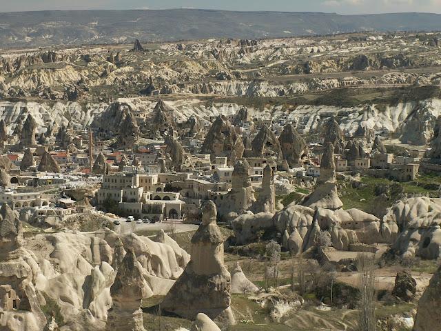 Каменные столбы  Именно таким образом были образованы знаменитые «каменные столбы» перибаджалары (тур. Peri bacaları, «камины фей», англ. fairy chimney) — останцы в виде каменных грибов и каменных столбов причудливых форм и очертаний. Геологический разрез этих образований выглядит следующим образом: наверху расположены базальты и андезиты а внизу — туфы  Долина Паша Баглари (Пашабаг). Невшехир, Аванос, Чавушин, нац. парк Гёреме Ранее базальты и андезиты покрывали туфовую основу полностью, теперь же (благодаря процессу разрушения) увидеть их можно только в отдельных частях скал: они нависают крупными блоками («шляпками») на конусообразных туфовых столбах. Под ними видна четкая горизонтальная линия, обозначающая границу скалы и туфа. Шейка туфового конуса со временем постепенно утончается, благодаря чему в какой-то момент эта «шляпка» будет обрушена. Не защищённые сверху останцы разрушаются полностью. Процесс их образования и разрушения, проявившийся в четвертичном периоде, продолжается и до наших дней.  Туфовые конусы высятся либо сплошной стеной, либо отдельными группами. Некоторые из этих скал достигают высоты 40 м. Этот вид образований считается присущим исключительно Каппадокии: 18-ти километровая территория Кызыл-Ирмака, Дамса-Чайы (на востоке), Невшехир-Чайы (на западе), а на юге 288 кв.м. между Ойлы и Кермильскими горами. Типичная форма — «грибы», хотя есть и более экзотические формы. Так, в окрестностях Гёреме находится т. н. Love Valley (Нижняя долина, она же Долина пенисов, Penis Valley), скальные образования которых имеют очевидные формы фаллосов  В окрестностях г. Кула в Эгейском регионе Турции имеется по аналогии названная область «Куладоккия», площадью 37,5 гектар, образовавшаяся схожим образом из вулканических пород.