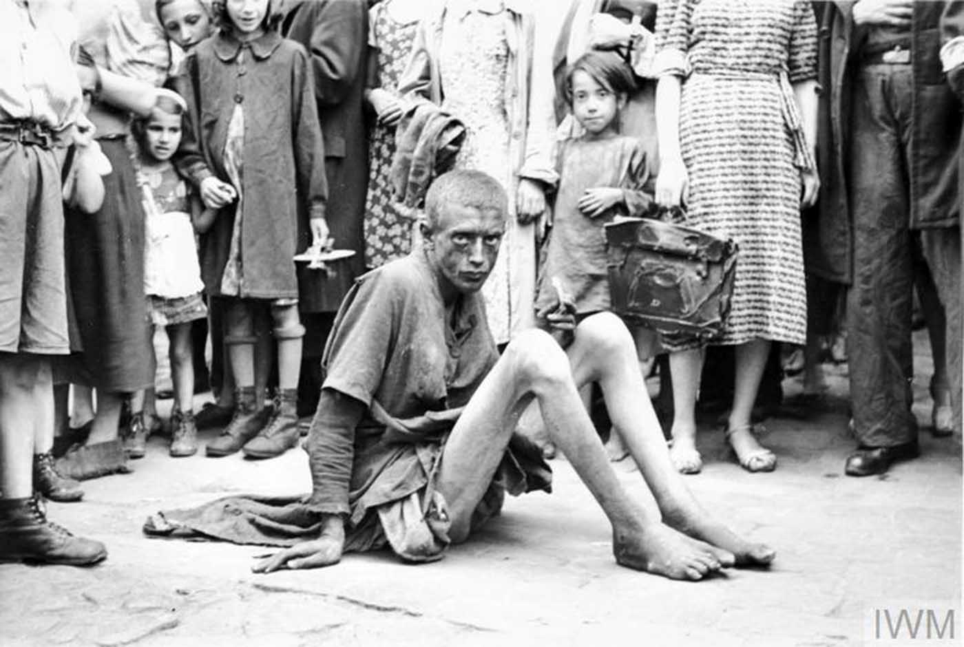 An emaciated boy sitting on a pavement. Note a crowd of pedestrians around him, including children with toys.