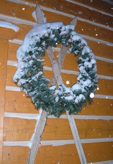 Exterior winter day, snowing, with a large Christmas wreath and lights hanging on the log sided condo over antique skis.