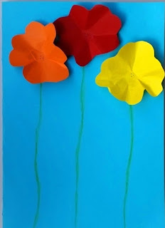 A Mothers' Day card, home-made of light blue card. Three flowers are lined up side by side. The stems are drawn with green pencil. The flower heads are made of paper circles which have scalloped edges folded upwards to make petals raised above the card. Each flower head has a flat centre glued against the card. From left to right the flowers are orange, red and yellow with the centre red flower slightly taller than the other two.