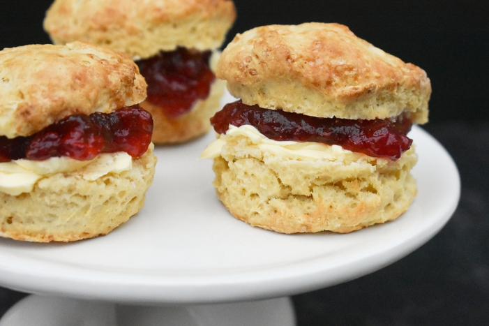Buttery Scottish Teatime Scones filled with jam on a white cake stand