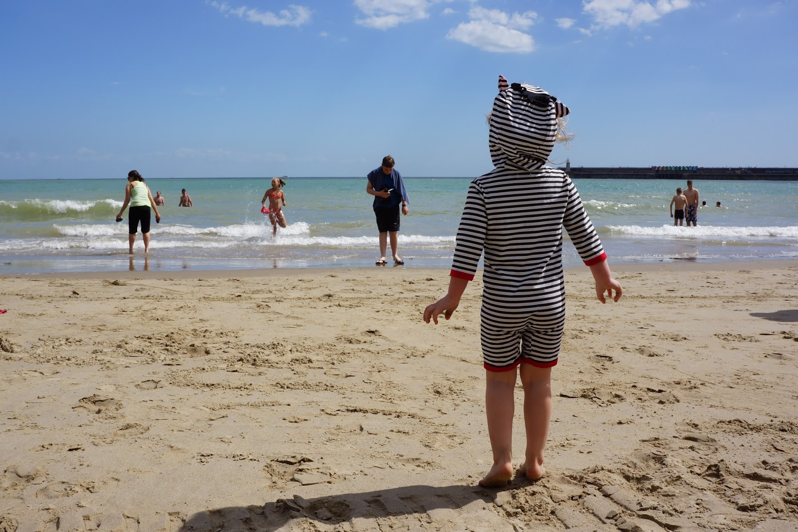 toddler wearing a zebra swimsuit looking out at the sea