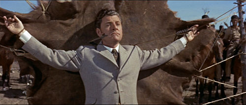 Kenneth More tied up with arrows being fired at him
