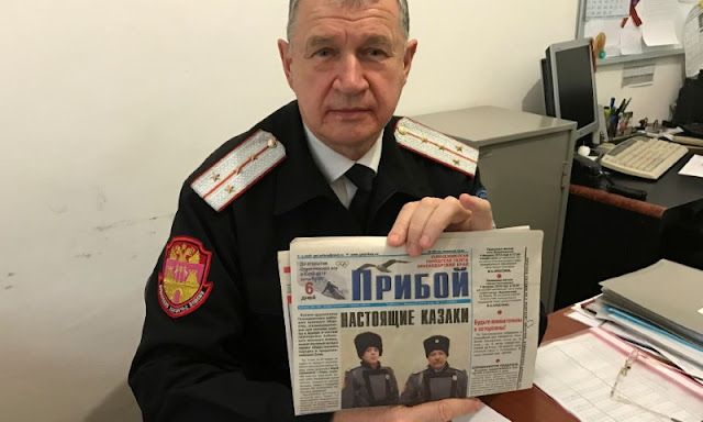 Image Attribute:  Russian Cossack commander Vladimir Bagliy shows a local newspaper with a picture of his fellow Cossack Yuri Sokalsky (R) killed near the Syrian city of Palmyra, in the Black Sea town of Gelendzhik, Russia, March 16, 2017. REUTERS/Maria Tsvetkova
