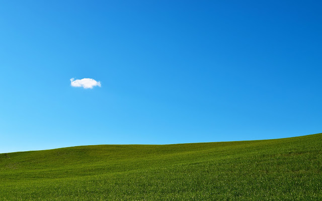 Blue skies, green grass and a small solitary cloud