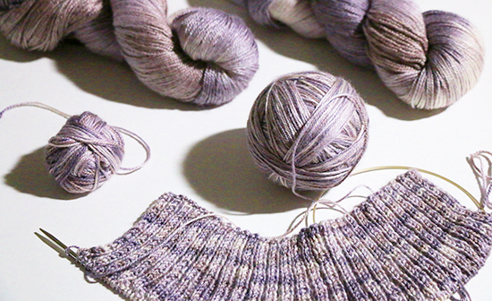 Skeins and Balls of Sport Weight Purple Yarn with Knit Sweater Ribbing in Progress