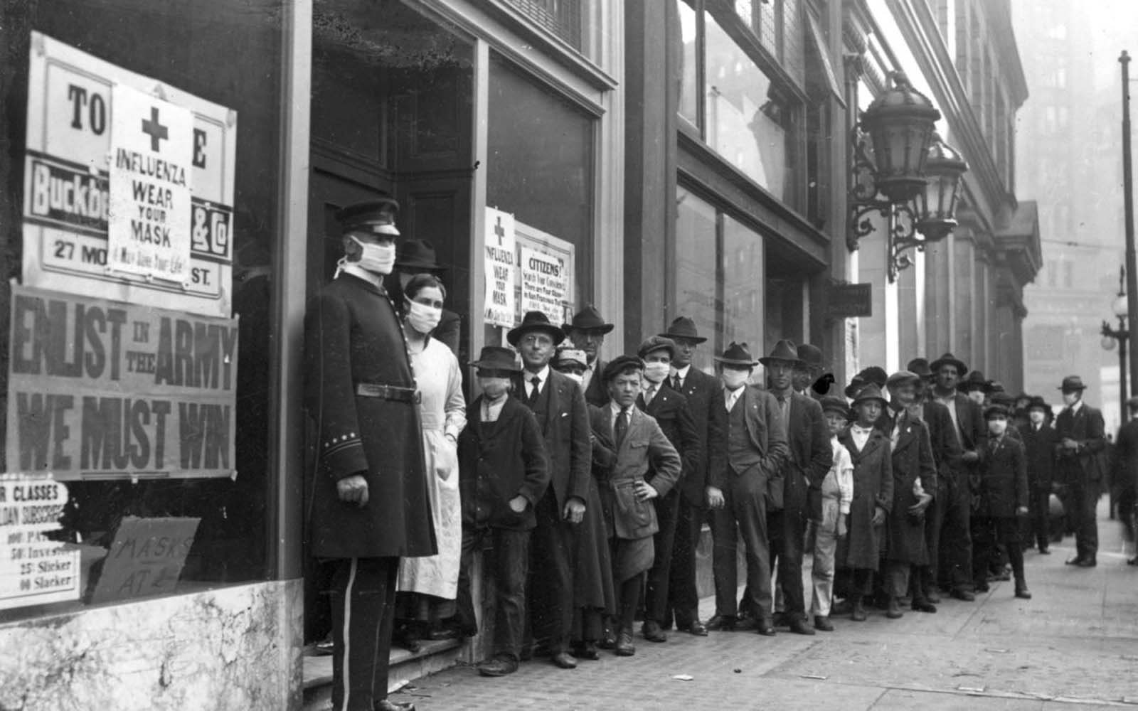 eople wait in line to get flu masks on Montgomery Street in San Francisco in 1918.