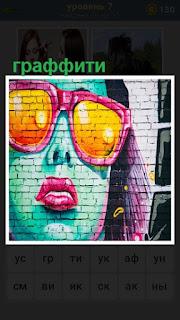 На кирпичной стене нарисовано женское лицо граффити