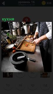 На кухне повар занимается приготовлением еды, режет на разделочной доске