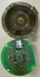 Codificador absoluto de código Gray con 13 pistas. En la parte superior se puede ver el receptáculo, el disco del interruptor y la fuente de luz. En la parte inferior se puede ver el elemento de detección y componentes de soporte