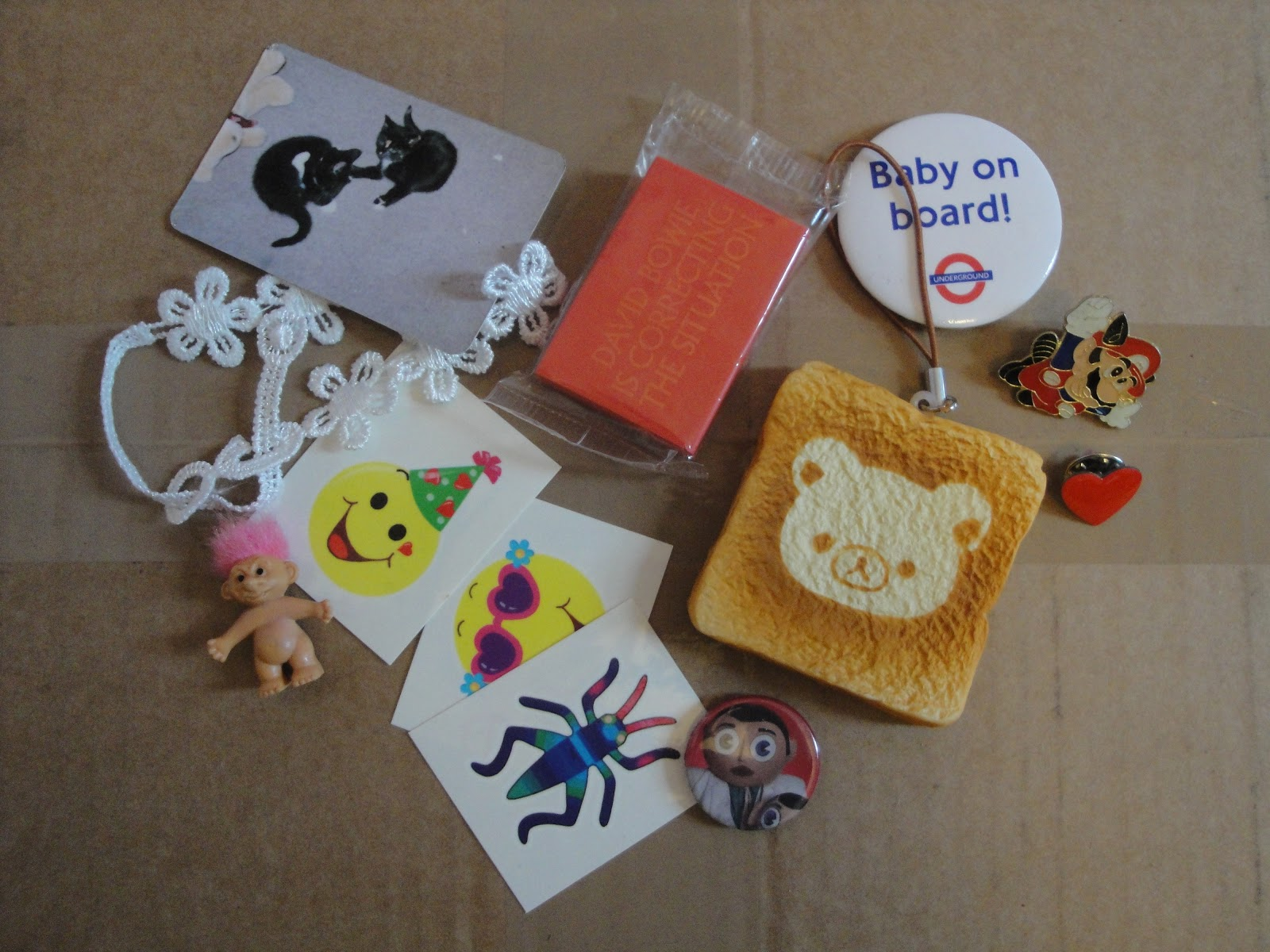 An assortment of items including a photo of two cats, a small troll doll, several badges, a white flowery bracelet, temporary tattoos and a red eraser.