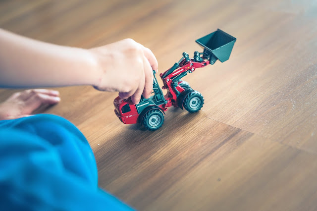 Photo of child playing with toy truck at home