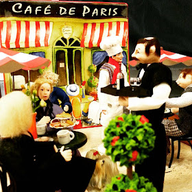 One-twelfth scale miniature french cafe scene with diners outdoors under umbrellas.
