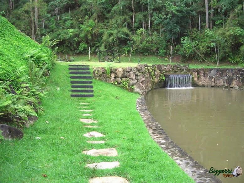 Caminho de pedra com pedra santo mé com a construção dos lagos com os muros de pedra rústica com a escada de dormente de madeira. No pé do talude o detalhe do murinho com pedra.