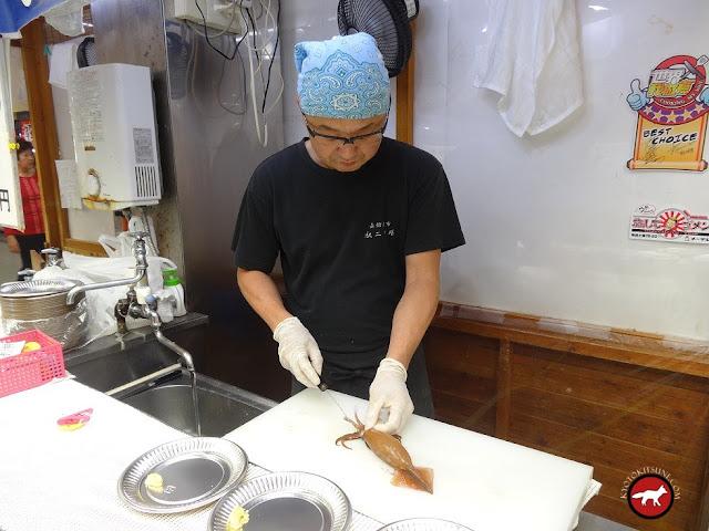 Chef japonais qui découpe un calamar vivant
