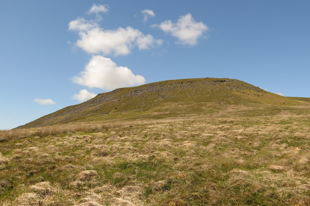 A green hillside, its upper reaches studded with boulders, rises up from pale grassland against a blue sky and occasional white cloud.