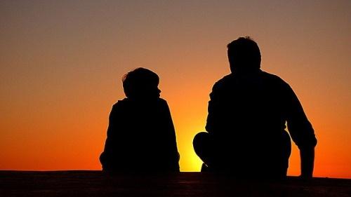 Silhueta de pai e filho ao pôr do sol. #PraCegoVer