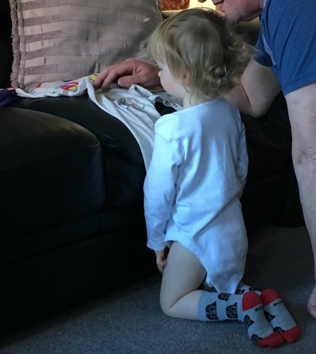 toddler kneeling next to adult looking at pyjama's