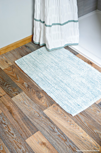Wood look vinyl flooring updates a builder basic bathroom with rustic modern finishes.