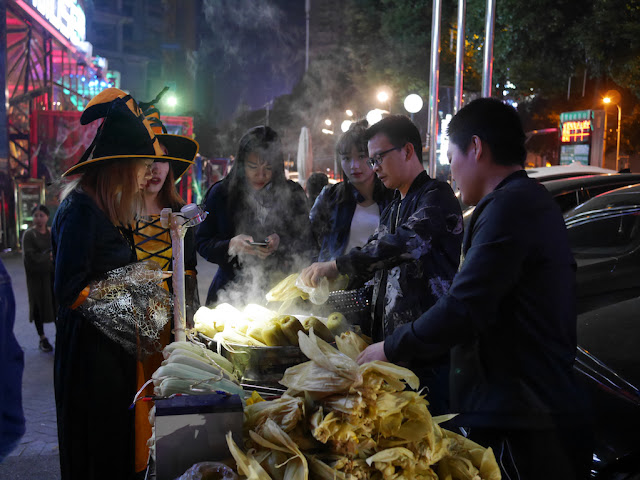 two young women dressed up for Halloween buying corn in Changsha
