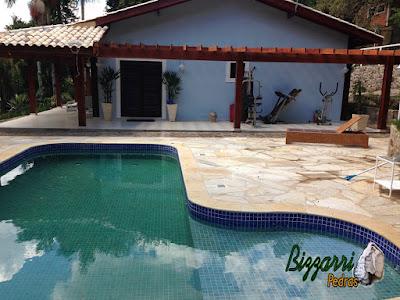 Construção da piscina de concreto revestida com azulejo com o piso de pedra São Tomé tipo caco em residência com o pergolado de madeira em condomínio em Atibaia-SP.