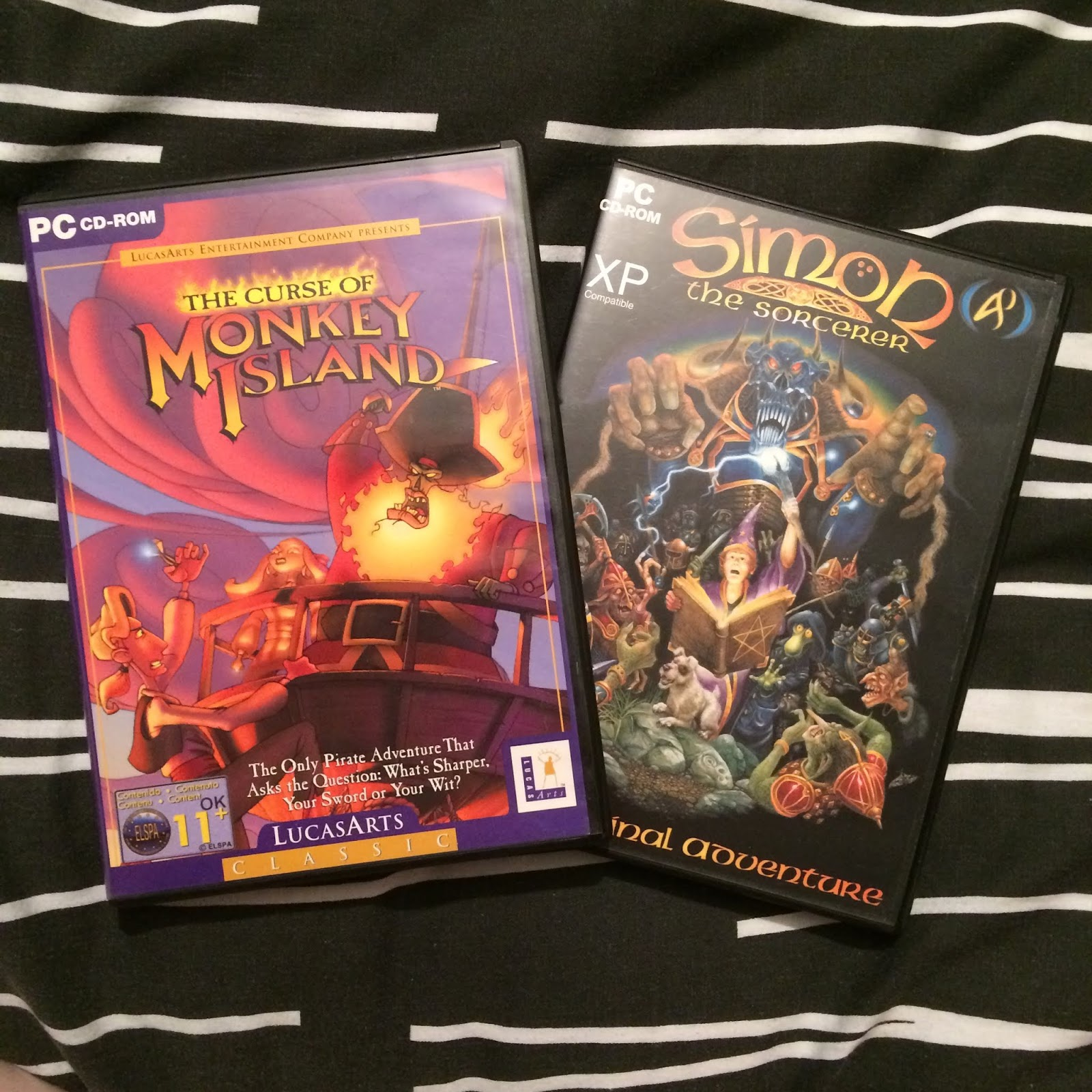 A photo of the cases for The Curse of Monkey Island and Simon the Sorcerer
