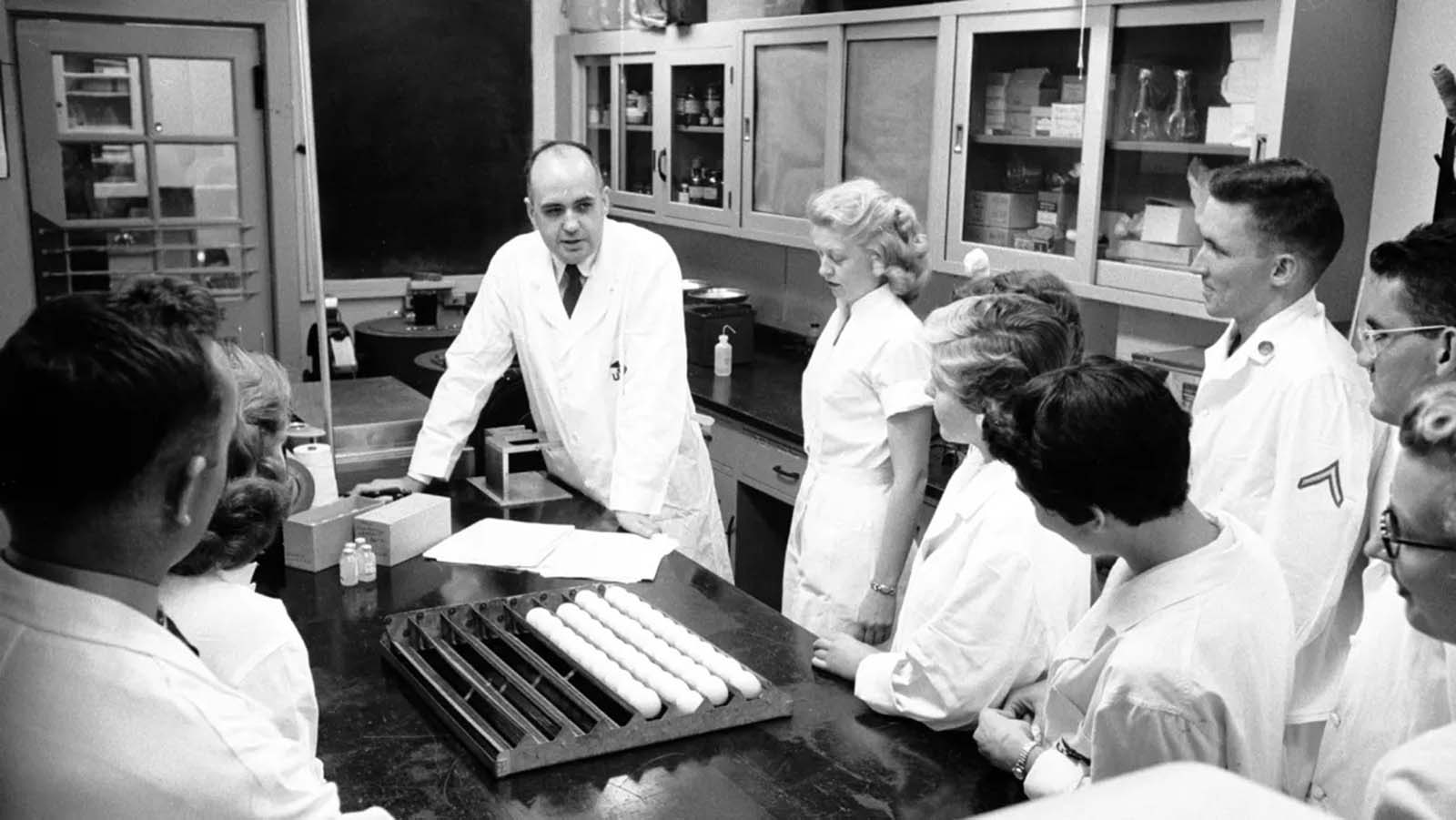 Dr. Maurice Hilleman, pictured center, talking with his research team as they study the flu virus in a lab at Walter Reed Army Institute of Research in Silver Springs, Maryland, 1957.