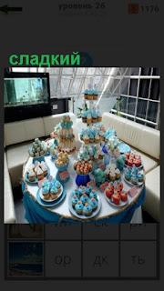 на столе поставлены блюда с тортами и другими сладостями
