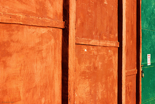Minimalist Photo of Lines on an Orange Textured Indian wall with a Green Door.