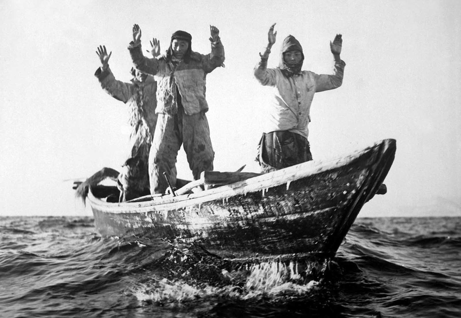 Three Korean Communists in a fishing boat are captured by the USS Manchester off the coast of Korea on May 10, 1951.