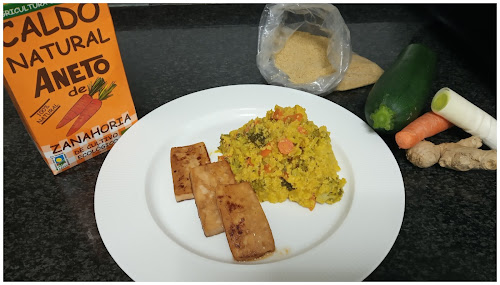 Emplatado del cuscús con el tofu. Detrás un brick de caldo aneto de zanahoria y bolsa con cuscús