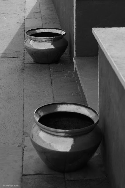 A Black and White Minimal Art Photograph of Two Brass Pot placed near the Stairs at City Palace, Jaipur. (India)