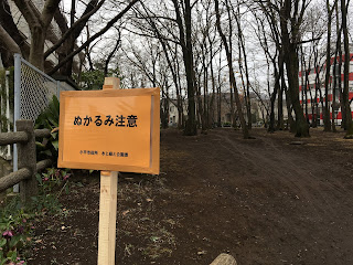 A picture of an orange sign at the entrance to a small copse telling people to be careful of the mud