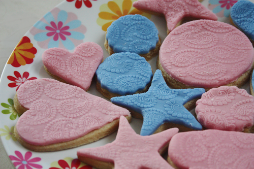 Paisley print embossed vanilla sugar cookies, in both pink and blue fondant, in heart, circle, and star shapes, on a plate