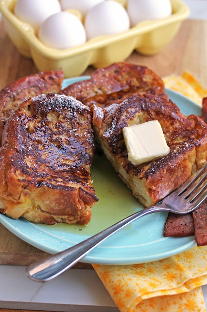 Eggnog French Toast topped with butter and syrup sitting on a plate next to bacon strips and a carton of eggs.