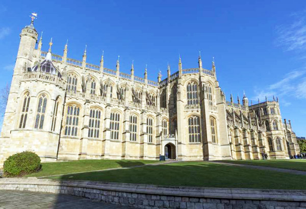 a large stone building with a clock tower: St. George's Chapel on the grounds of Windsor Castle in England is seen here.