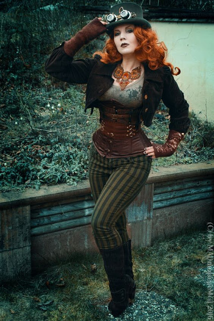 Steampunk redhead wearing top hat, goggles, striped pants, boots, underbust corset, lace top, arm warmers and jewelery (statement necklace) color palette: orange, browns, and greens