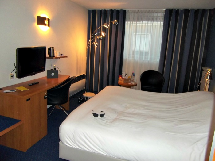 White linen bed, desk and Tv in Inntel room