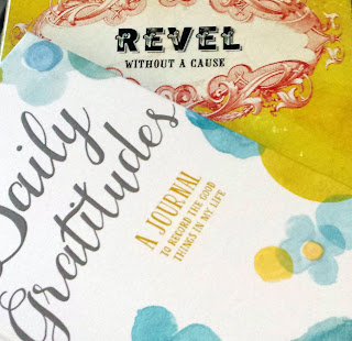 "A yellow journal titled ""Revel Without a Cause"" underneath a white journal titled ""Daily Gratitudes"""