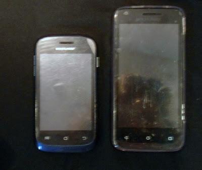 Foto com dois modelos de Smathphone da mesma empresa sob um fundo escuro