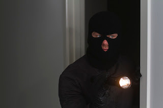 Picture of a masked burglar with a flashlight.